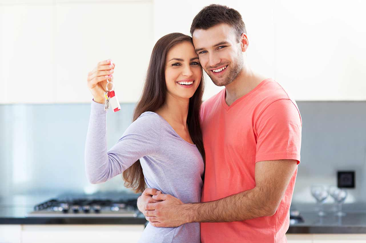 happy couple owning a house