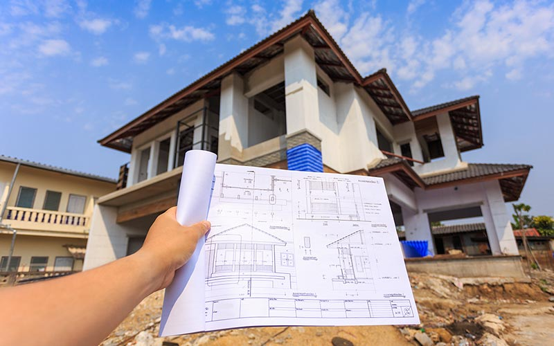 new house with plans in foreground